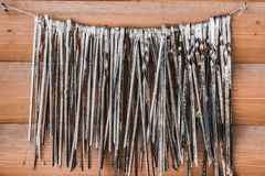 A Big Group Of Old Metal Skewers For Meat Is On A Wire On Two Nails On An Orange Wooden Boards Wall Background Stock Photo