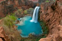 Free A Bird`s Eye View Of The 100ft Havasu Falls And Its Beautiful Deep Blue Pool Beneath, Surrounded By Thick, Green Vegetation. Stock Photos - 135377433