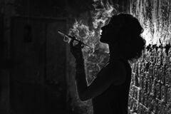 Free A Black And White Silhouette Portrait Of A Young Woman Smoking A Cigarette In A Mouthpiece. Royalty Free Stock Photography - 193816947