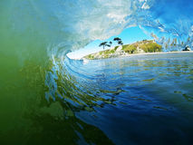A Blue And Green Ocean Wave Breaks Near The Beach Royalty Free Stock Photography