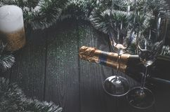 A Bottle Of Champagne And Two Glasses Stand On A Dark Gray Wooden Table Surrounded By Christmas Decorations And A White-gold Royalty Free Stock Images