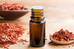 Free A Bottle Of Sandalwood Essential Oil With Sandalwood On A Wooden Royalty Free Stock Photography - 107529047