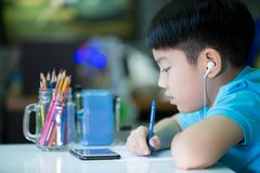 Free A Boy Using Cellphone And Painting On A White Paper At Home Royalty Free Stock Image - 56583026