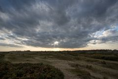 Free A Break In The Clouds. Bleak Landscape With Distant Sun Breaking Stock Image - 108403001