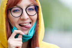 Free A Bright Girl With Glasses And Braces Joyfully Removes The Medical Mask From Her Face, Mimics And Shows Her Tongue Stock Photos - 182862513
