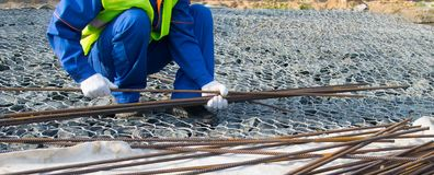 Free A Builder In A Blue Uniform, Against The Background Of Stones, Takes Long Metal Rods For The Construction Of Concrete Structures, Royalty Free Stock Photography - 153855117