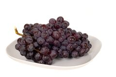 A Bunch Of Juicy Red Grapes On A White Plate Stock Image