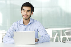 A Businessman Sitting At A Desk, Typing At A Laptop, Thinking Stock Image