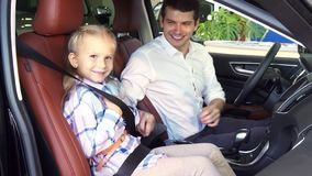 Free A Caring Father Fastens His Daughter`s Seat Belts In The Car Stock Photos - 128690323
