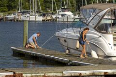Free A Caucasian Couple Is Docking Their Cabin Cruiser Boat Stock Photos - 195011003
