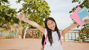 Free A Charming Philippine Schoolgirl With A Backpack And Books In A Park Off The Coast. A Girl Joyfully Poses, Raising Her Royalty Free Stock Photography - 130975967