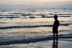 Free A Child Stands In The Sea Of Sunset In Krabi, Thailand. Stock Images - 126931254
