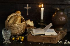 Free A Christmas Table, Bread In A Basket And A Glass Of Water Bring A Prayer Book To A Dark Wooden Table. Cross In The Background Stock Photo - 164676410