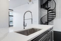 Free A Chrome Kitchen Sink With A White Counter Top. Stock Photo - 194584490