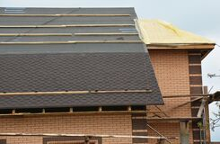 Free A Close-up On A Roofing Construction With Asphalt Roof Shingles Installation On The Waterproof Underlayment And Uncovered Roof Stock Image - 183372721