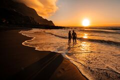 Free A Couple In Love Stands In The Ocean In The Evening Looking At The Beautiful Sunset On The Island Of Tenerife.Spain Royalty Free Stock Photos - 214271868