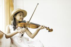 Free A Cute Asian Elementary School Girl Is Playing A Violin Happily Royalty Free Stock Photo - 188256165