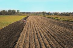 A Farmer On A Red Tractor With A Seeder Sows Grain In Plowed Land In A Private Field In The Village Area. Mechanization Of Spring Stock Photography