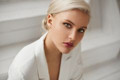 Free A Fashionable Young Woman With Perfect Blond Hair And Perfect Trendy Makeup In An Elegant White Suit Posing In Studio Stock Photos - 161009893