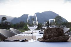 A Fine Dinner Table Set With High Wine Glass And Utensils With A Weave Hat On The Table With Mountain View. Stock Photos