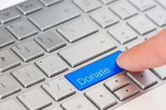 Free A Finger Press Blue Donate Button On Laptop Keyboard Royalty Free Stock Photography - 114479187