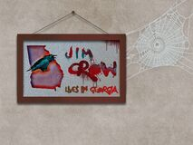 Free A Framed Picture Of A Crow Sitting On A Map Of The State Of Georgia, US As A Cobweb Hangs From The Outdated Jim Crow Concept In Th Stock Image - 214402341