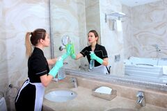 Free A Girl In A Cleaning Service Uniform Cleans A Large Mirror In The Bathroom. The Concept Of Cleanliness And Disinfection In The Stock Images - 182165154
