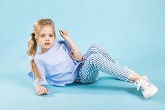 Free A Girl In Blue Clothes Is Sitting On A Blue Background. Royalty Free Stock Photography - 120509137