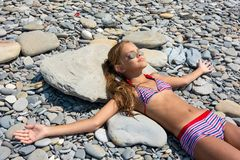 Free A Girl Lies On The Stones Of A Rocky Beach And Sunbathes Stock Images - 154859824