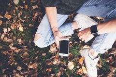 Free A Girl Sits On The Grass And On Fallen Autumn Leaves With Smartp Stock Photography - 124317262