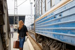 A Girl With A Suitcase Is Standing Near A Passenger Train Stock Image