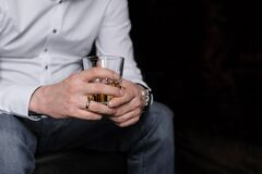 Free A Glass Of Drink In The Men`s Hands Royalty Free Stock Photography - 182843197