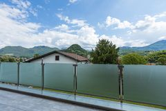 Free A Glass Parapet Of A Modern Building Balcony Overlooking Hills Royalty Free Stock Photo - 150202155