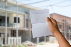 A Hand Holding Saving Account Bank Book On Construction House Stock Photo