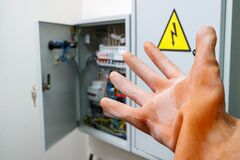 Free A Hand In A Dielectric Glove Reaches For The Electrical Panel Stock Photo - 190569270