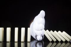 A Hand In A Glove Stops The Dominoes Falling Royalty Free Stock Photo