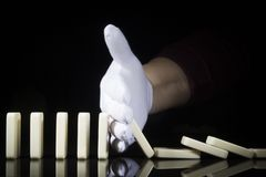 A Hand In A Glove Stops The Dominoes Falling Royalty Free Stock Images