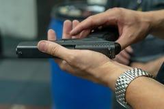 A Hand Of Man Practicing Firing Using A Glock Gun Model At The Shooting Range. Fire Glock Hand Gun. Man`s Hands Loading A Pistol Royalty Free Stock Photography