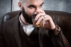 A Handsome Brutal Young Stylish Brunette Man With A Beard Sits In A Leather Chair On A Gray Background, Drinks Whiskey Stock Image
