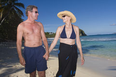 A Happy Couple Walking On The Beach Royalty Free Stock Photo