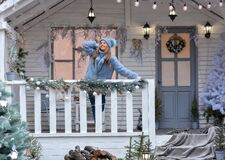 Free A Happy Girl Model In A Deep Hat, Fur Coat, Gloves Is Standing On The Porch Of The Christmas House! Happy New Year And Merry Stock Image - 203829841