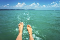 Free A Happy Girl Woman Is Kicking Feet On A Sea Lake And Splashing Water On A Sail Boat Summertime Stock Images - 150348084