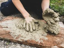 Free A Kid Kneads And Models Wet Clay On A Wooden Plank On The Floor Stock Images - 166204274