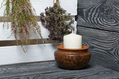 Free A Large Candle In A Clay Vessel. Bunches Of Fragrant Herbs Hang Nearby. Stands On Painted Boards Painted In Black And White Royalty Free Stock Image - 169322096