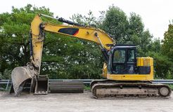 Free A Large Excavator In Yellow Color Visible From The Profile With A Lowered Bucket. Stock Images - 165465014