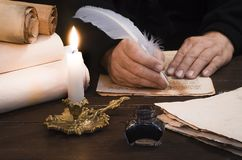 Free A Lit Candle Against The Background Of Blurred Scrolls, Writer`s Hand, Books And Bird`s Feather Stock Photography - 159610952