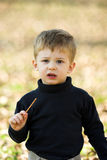A Little Boy Eating Short Stick Royalty Free Stock Photography