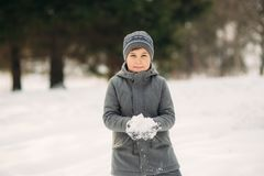 A Little Boy Walks In The Park In The Winter Weather, Play Snowballs And Rejoiced. Waiting For Christmas Mood Stock Photo