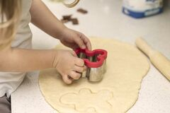 Free A Little Girl 3-5 Years Old Cuts Out Cookies From The Dough Using A Cookie Cutter Royalty Free Stock Photos - 179713028