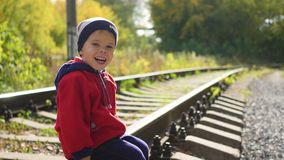 Free A Lonely Boy Sitting On The Railroad Tracks. Dangerous Games And Entertainment Stock Image - 100140411